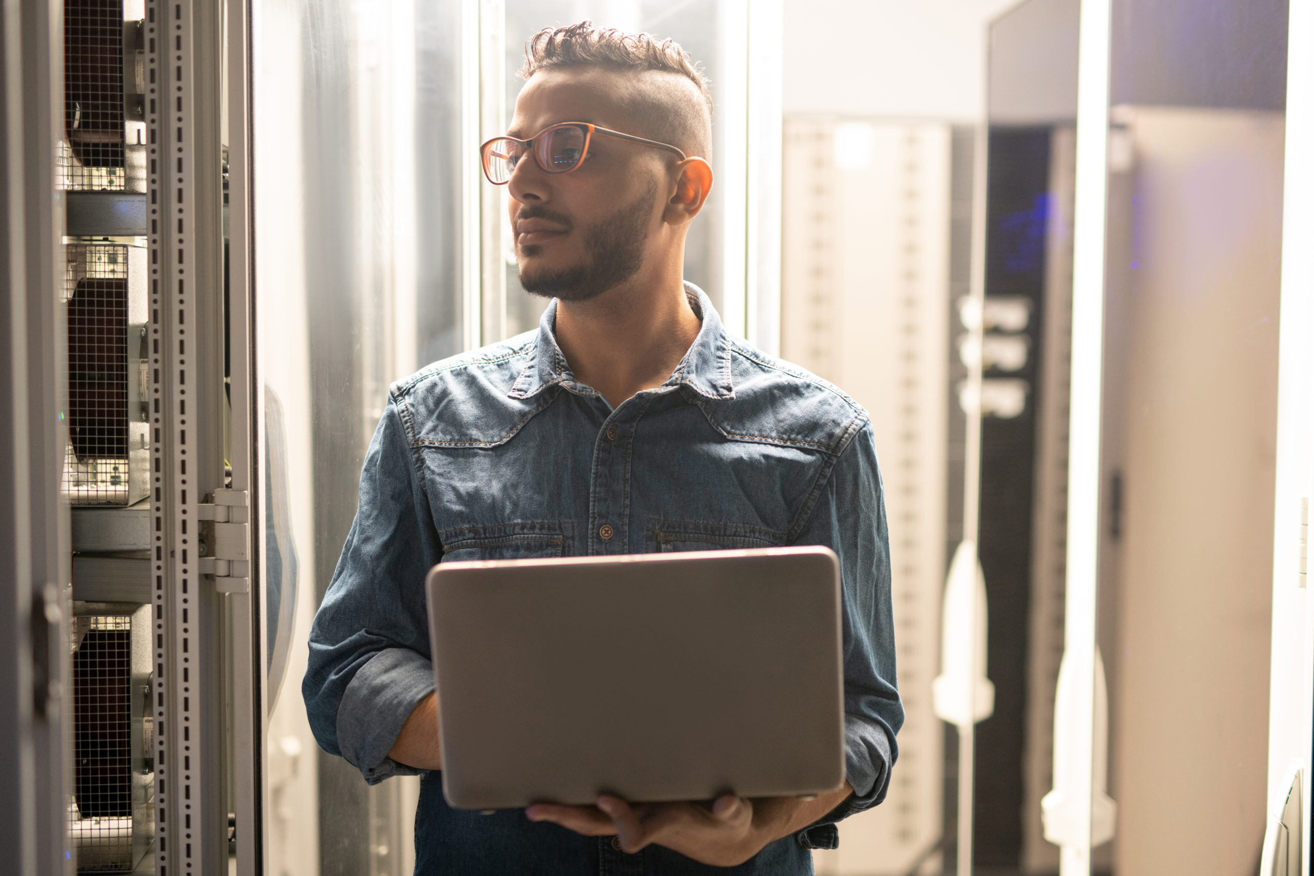 Serious confident young Arabian IT engineer with beard standing in data center and using laptop while providing safety of network server